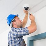 technician-adjusting-cctv-camera-close-up-ceiling-50590394